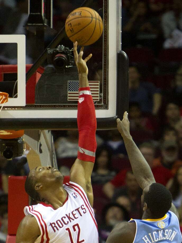 Rockets power forward Dwight Howard, left, blocks a shot by Nuggets power forward J.J. Hickson. Photo: Cody Duty, Houston Chronicle