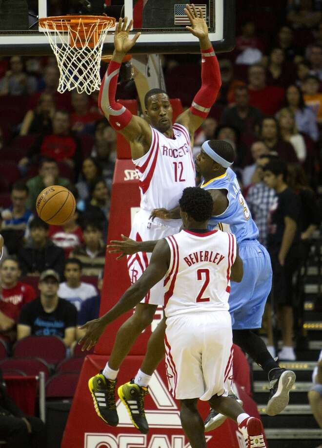 Rockets power forward Dwight Howard, center, and point guard Patrick Beverley, defend as Nuggets point guard Ty Lawson loses control of the ball. Photo: Cody Duty, Houston Chronicle