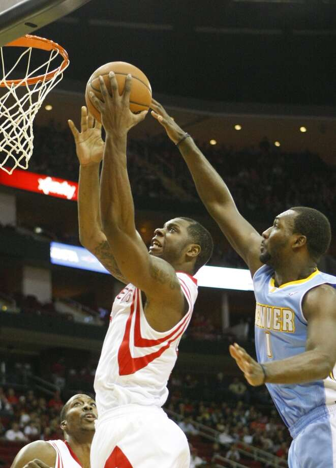 Rockets power forward Terrence Jones, left, shoots past Nuggets small forward Jordan Hamilton. Photo: Cody Duty, Houston Chronicle