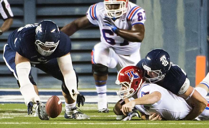 Rice defensive tackle Christian Covington (56) scoops up a fumble by Louisiana Tech quarterback Paul