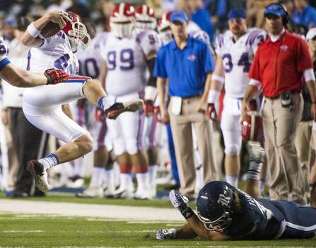 Louisiana Tech punter Logan McPherson is upended as he picks up a first down on a fake punt during the first half. Photo: Smiley N. Pool, Houston Chronicle