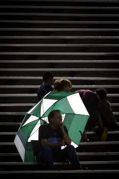 A fan takes cover under an umbrella as a light rain falls on a college football game between Rice and Louisiana Tech at Rice Stadium. Photo: Smiley N. Pool, Houston Chronicle