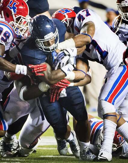 Rice running back Jawon Davis is wrapped up by Louisiana Tech defensive back Xavier Woods (39) and l