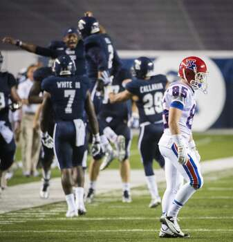 Louisiana Tech wide receiver Trent Taylor (85) walks back to the bench as Rice safety Malcolm Hill (2) celebrates after intercepting a pass intended for Taylor during the second half. Photo: Smiley N. Pool, Houston Chronicle