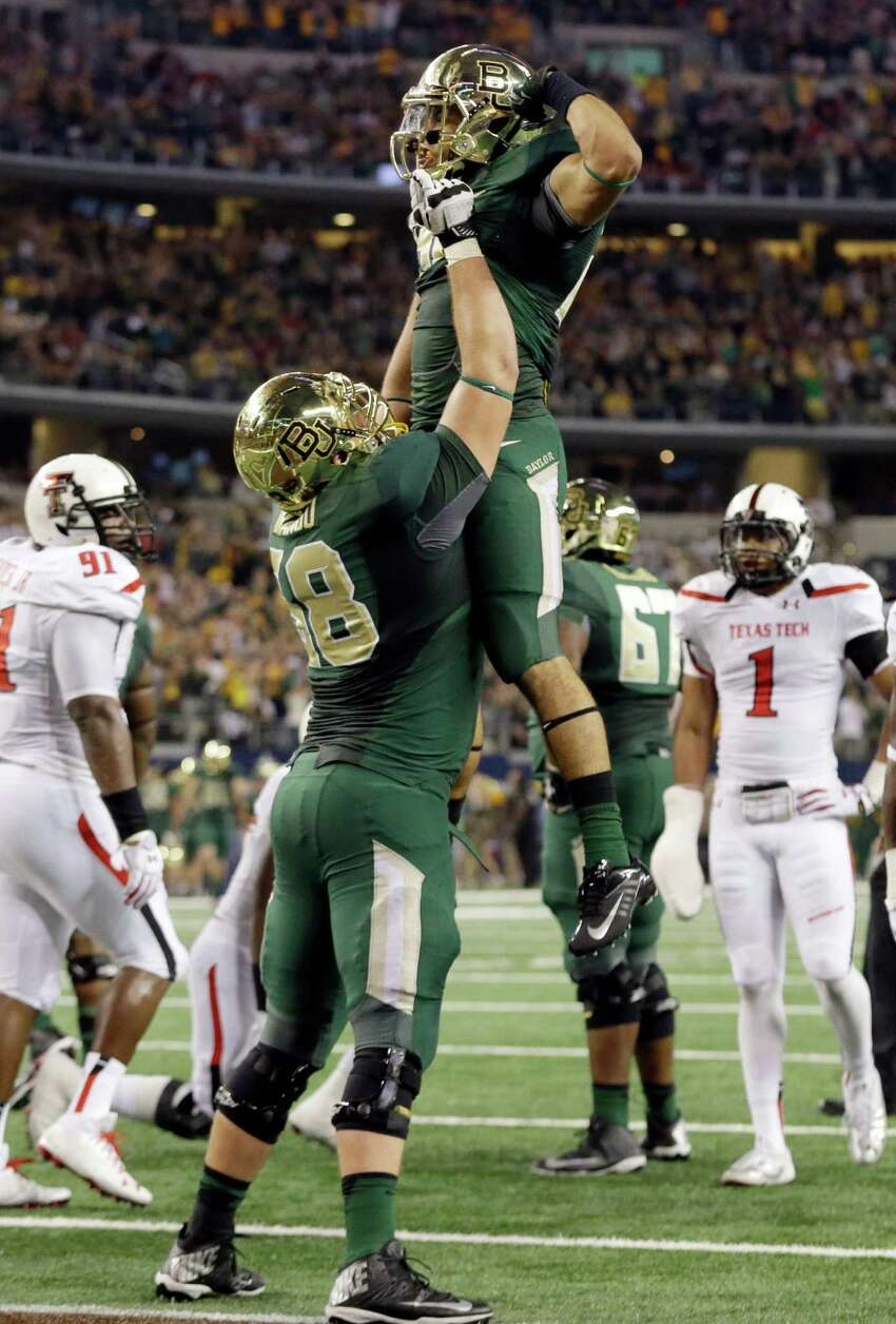 Baylor running back Devin Chafin, top, celebrates his touchdown with teammate offensive linesman Spencer Drango during the first half of an NCAA college football game against Texas Tech in Arlington, Texas, Saturday, Nov. 16, 2013. (AP Photo/LM Otero)