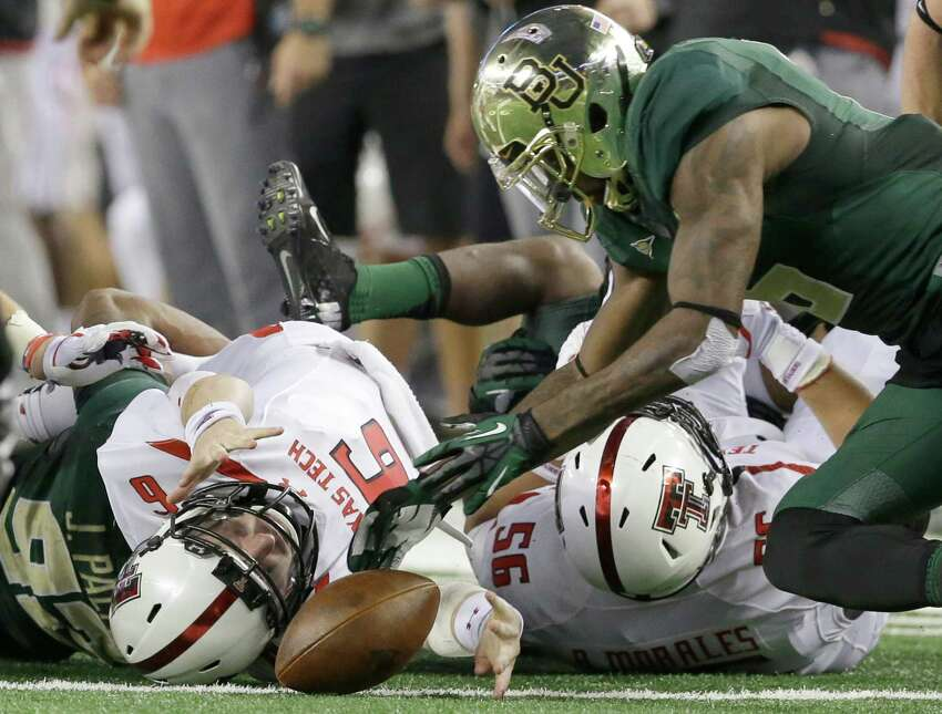 Texas Tech quarterback Baker Mayfield (6) fumbles as Baylor safety Ahmad Dixon, right, comes in to recover the loose ball during the first half of an NCAA college football game in Arlington, Texas, Saturday, Nov. 16, 2013. (AP Photo/LM Otero)