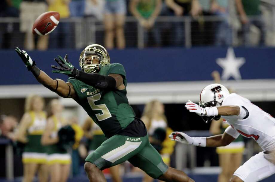 Baylor wide receiver Antwan Goodley (5) reaches for a pass against Texas Tech defensive back Justis Nelson, right, during the first half of an NCAA college football game in Arlington, Texas, Saturday, Nov. 16, 2013. (AP Photo/LM Otero) Photo: LM Otero, Associated Press / AP