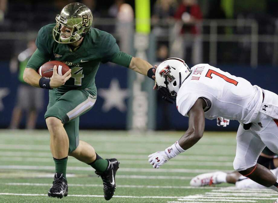 Baylor quarterback Bryce Petty, left, runs on the keeper against Texas Tech linebacker Will Smith (7) during the first half of an NCAA college football game in Arlington, Texas, Saturday, Nov. 16, 2013. (AP Photo/LM Otero) Photo: LM Otero, Associated Press / AP