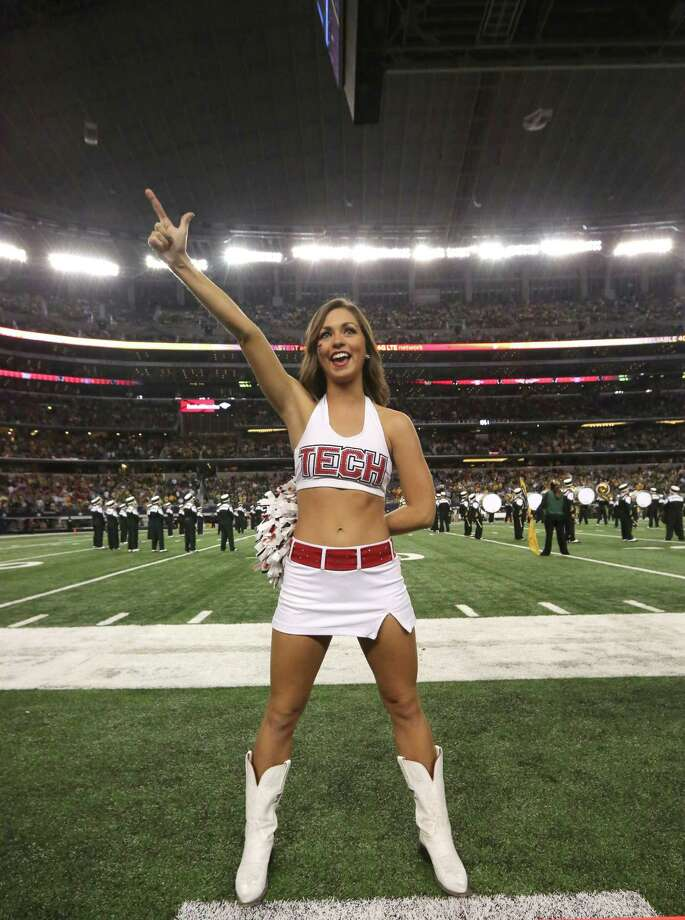 A Texas Tech cheerleader gives the guns up school salute before an NCAA college football game against the Baylor in Arlington, Texas, Saturday, Nov. 16, 2013. (AP Photo/LM Otero) Photo: LM Otero, Associated Press / AP