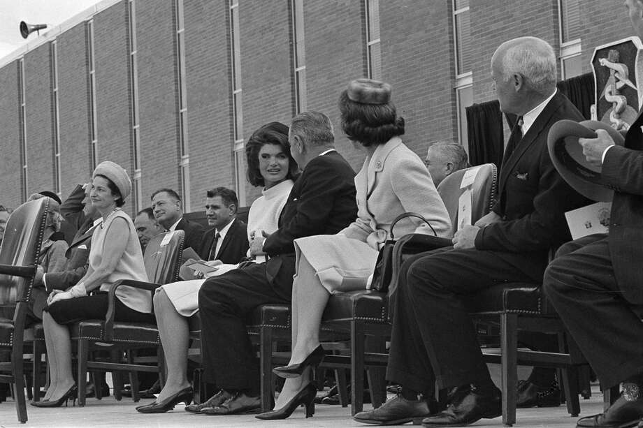 First Lady Jacqueline Kennedy chats with Vice President Lyndon B. Johnson as Nellie Connally looks on at right, during dedication ceremonies of the Aerospace Medical Center at Brooks Air Force Base in San Antonio, Nov. 21, 1963. Lady Bird Johnson is seated at left. Photo: Associated Press File Photo / AP