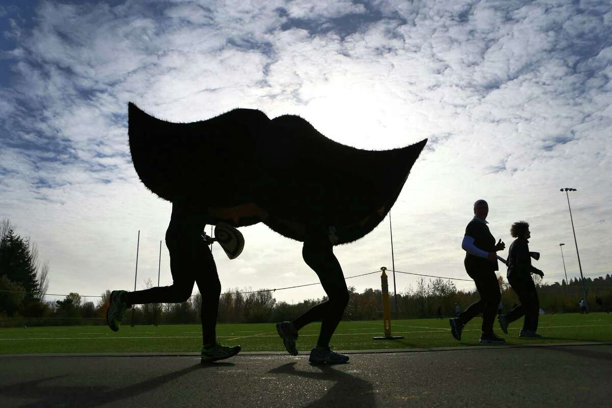 Erik Toth and Emma Toth run in a large mustache costume during the Mustache Dache 5K on Saturday, November 16, 2013 at Maguson Park in Seattle. During the race competitors ran with mustaches. More than 2,000 people participated in the run that helped raise money for Movember, an effort to support men's health.