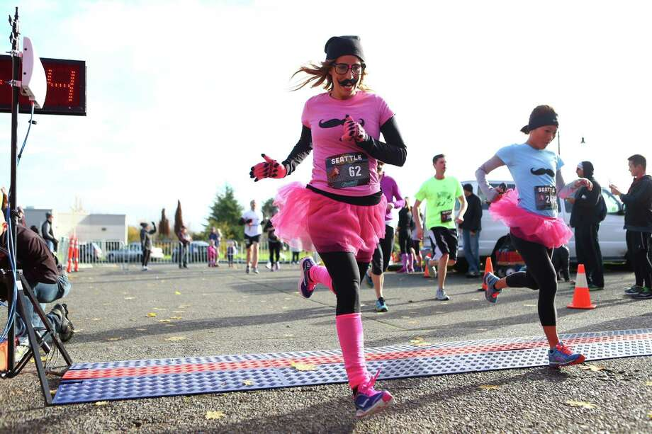 A competitor crosses the finish line during the Mustache Dache 5K on Saturday, November 16, 2013 at Maguson Park in Seattle. During the race competitors ran with mustaches. More than 2,000 people participated in the run that helped raise money for Movember, an effort to support men's health. Photo: JOSHUA TRUJILLO, SEATTLEPI.COM / SEATTLEPI.COM