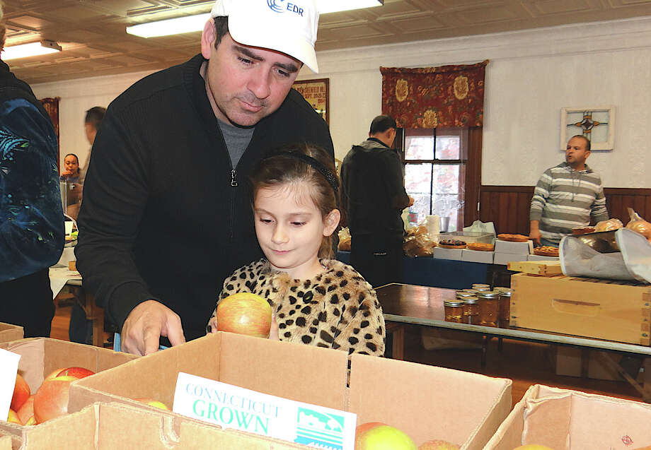 Ellery Walker, 6, and her father check out apples from Gazy Brothers Farm at the Greenfield Hill Grange's winter farm market on Saturday. Photo: Mike Lauterborn / Fairfield Citizen contributed