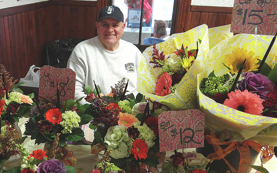 Sal Pace of Coreen's Bridge Floral Shop in Fairfield selling flowers Saturday at the Greenfield Hill Grange winter farm market. Photo: Mike Lauterborn / Fairfield Citizen contributed