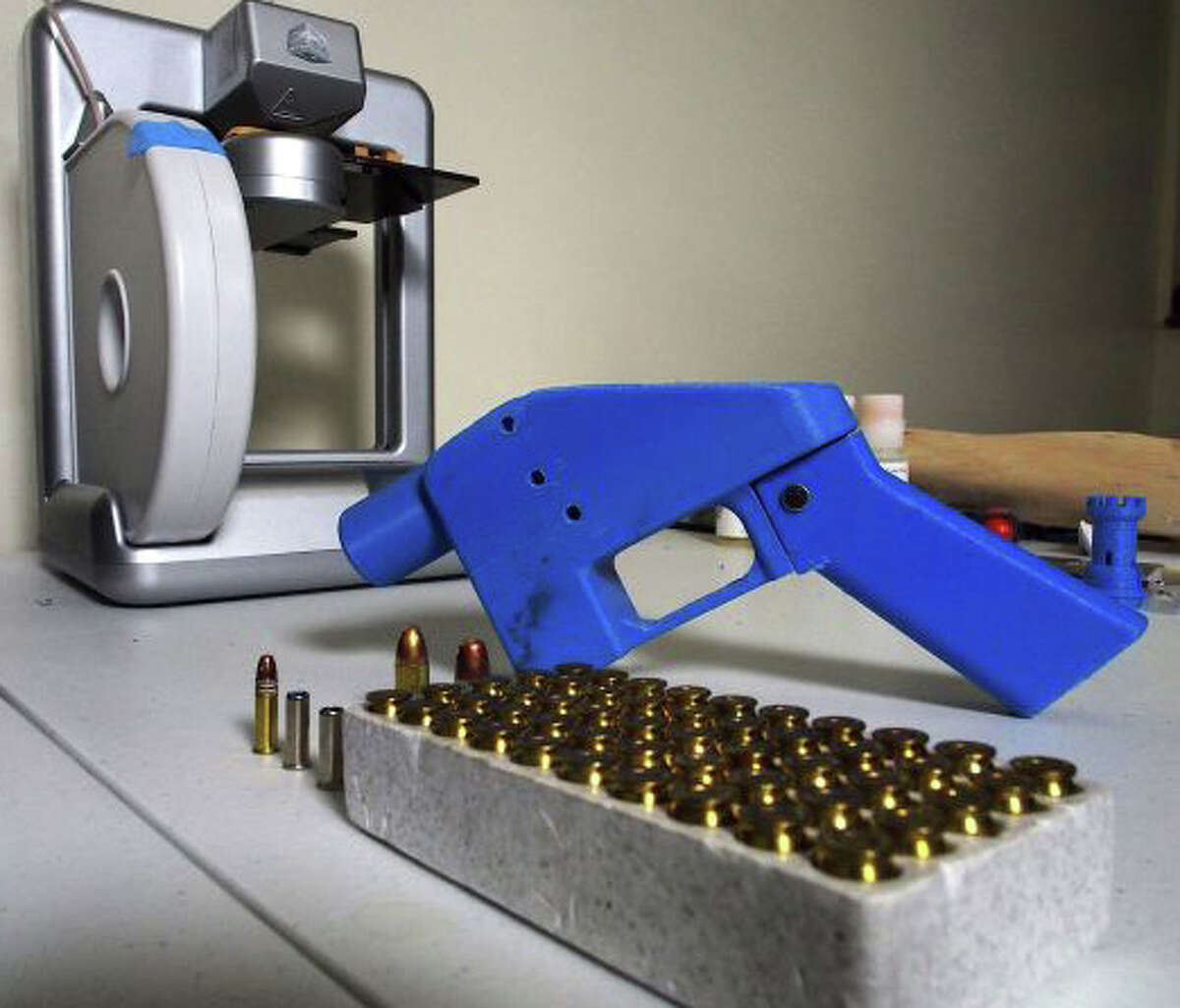A Liberator pistol appears next to the 3D printer on which its components were made. The single-shot handgun is the first firearm that can be made entirely with plastic components forged with a 3D printer and computer-aided design (CAD) files downloaded from the Internet.