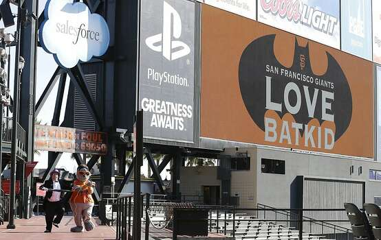 The scoreboard at AT&T Park displays a sign for Miles Scott, as Batkid, as the Penguin, bottom left, kidnaps San Francisco Giants mascot Lou Seal in San Francisco, Friday, Nov. 15, 2013. Photo: Jeff Chiu, Associated Press