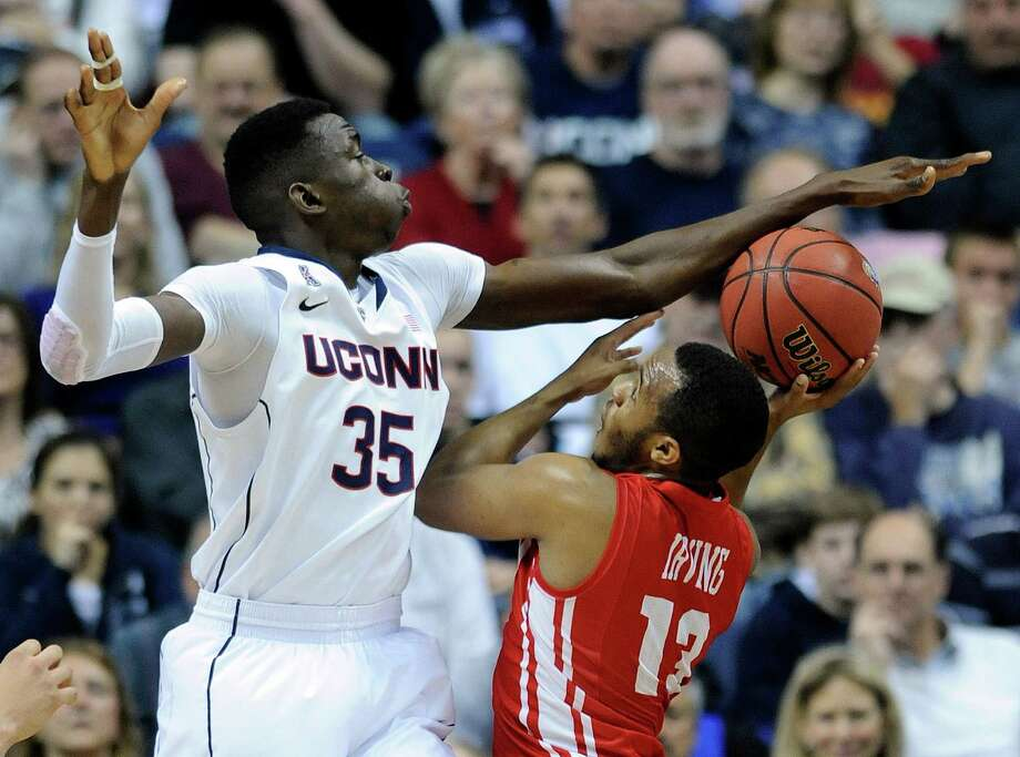 Connecticut's Amida Brimah (35) attempts to block the shot of Boston University's D.J. Irving (13) during the first half of an NCAA college basketball game in Storrs, Conn., on Sunday, Nov. 17, 2013. Photo: Fred Beckham, AP / Associated Press