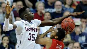 Connecticut's Amida Brimah (35) attempts to block the shot of Boston University's D.J. Irving (13) during the first half of an NCAA college basketball game in Storrs, Conn., on Sunday, Nov. 17, 2013.