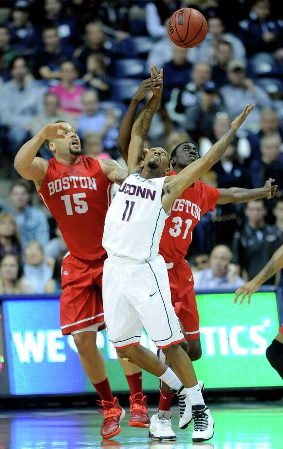 Boston University's Dom Morris (15) and Malik Thomas (31) fight for a rebound with Connecticut's Ryan Boatright (11) during the first half of an NCAA college basketball game in Storrs, Conn., on Sunday, Nov. 17, 2013. Photo: Fred Beckham, AP / Associated Press