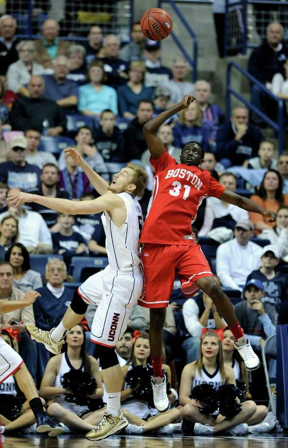 Connecticut's Niels Giffey (5) fights for a rebound with Boston University's Malik Thomas (31) during the first half of an NCAA college basketball game in Storrs, Conn., on Sunday, Nov. 17, 2013. Photo: Fred Beckham, AP / Associated Press