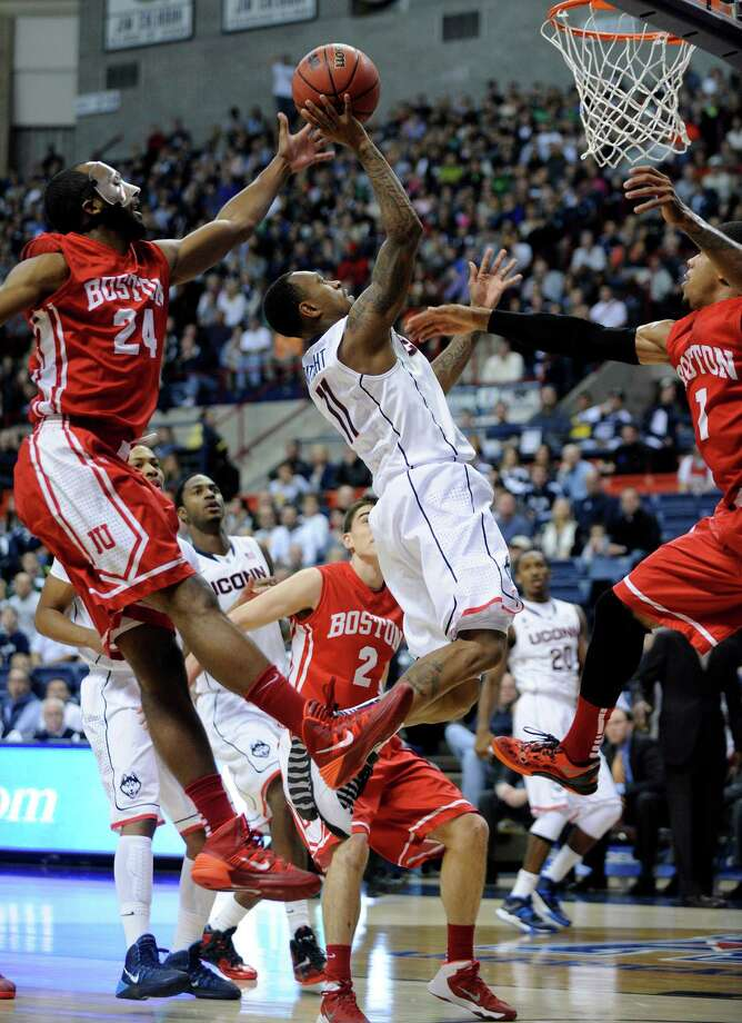 Connecticut's Ryan Boatright (11) drives past Boston University's Travis Robinson (24) and Maurice Watson Jr. (1) during the first half of an NCAA college basketball game in Storrs, Conn., on Sunday, Nov. 17, 2013. Photo: Fred Beckham, AP / Associated Press
