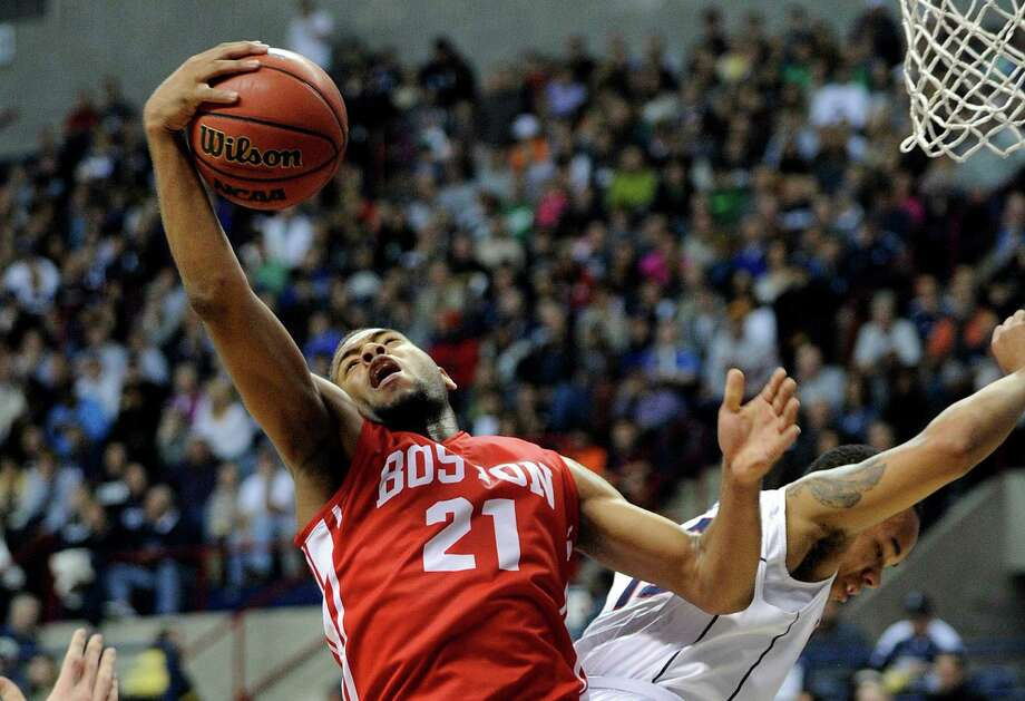 Boston University's Cedric Hankerson (21) fights for a rebound with Connecticut's Shabazz Napier during the first half of an NCAA college basketball game in Storrs, Conn., on Sunday, Nov. 17, 2013. Photo: Fred Beckham, AP / Associated Press