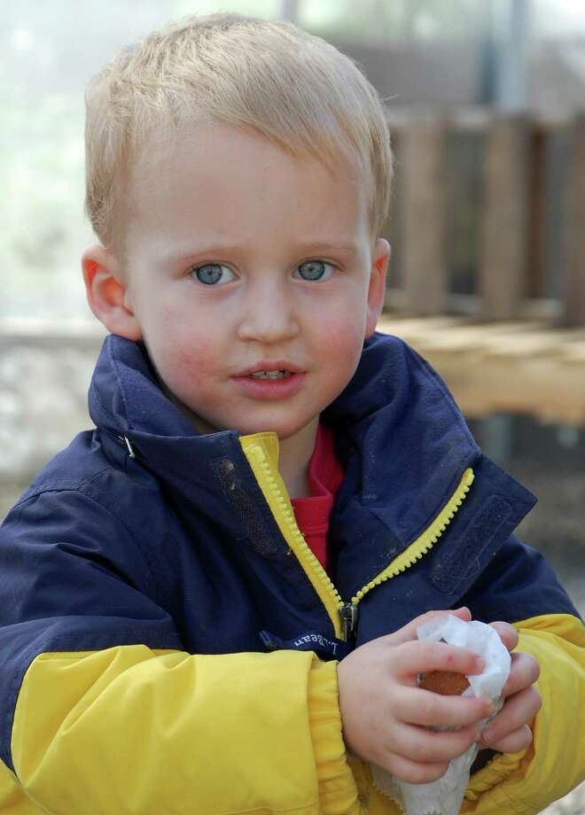 Max Borofsky of Easton, who is almost 2, enjoys a muffin Saturday at the first session of the Westport Winter Farmers Market. Photo: Jarret Liotta / Westport News contributed