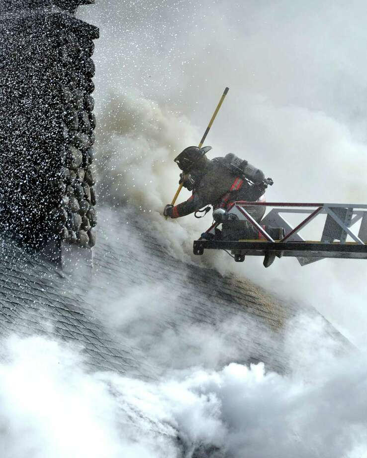 A firefighter from the McAdoo Fire Company Inc. is surrounded by smoke as he vents the roof during a fire at 887 Railroad Drive in Packer Township near Hazleton, Pa., on Wednesday, Nov. 13, 2013. The fire left a family of 4 homeless. Photo: Ellen F. O'Connell, AP / AP2013