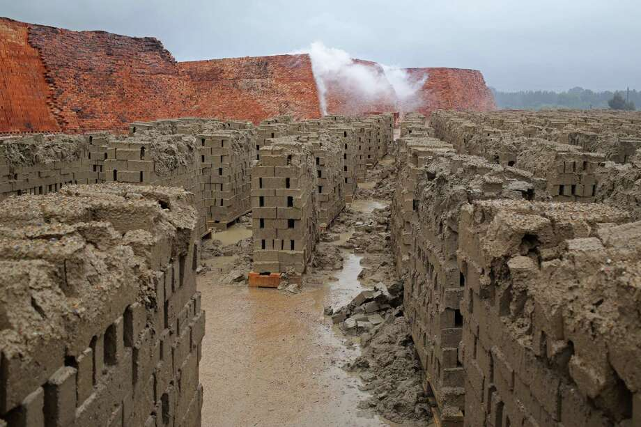 Newly made bricks that have not been dried through a heating process, disintegrate after heavy rain fall across the Western Cape province causing flooding during the weekend near Stellenbosch, South Africa, Saturday, Nov. 16, 2013. Photo: Schalk Van Zuydam, AP / AP