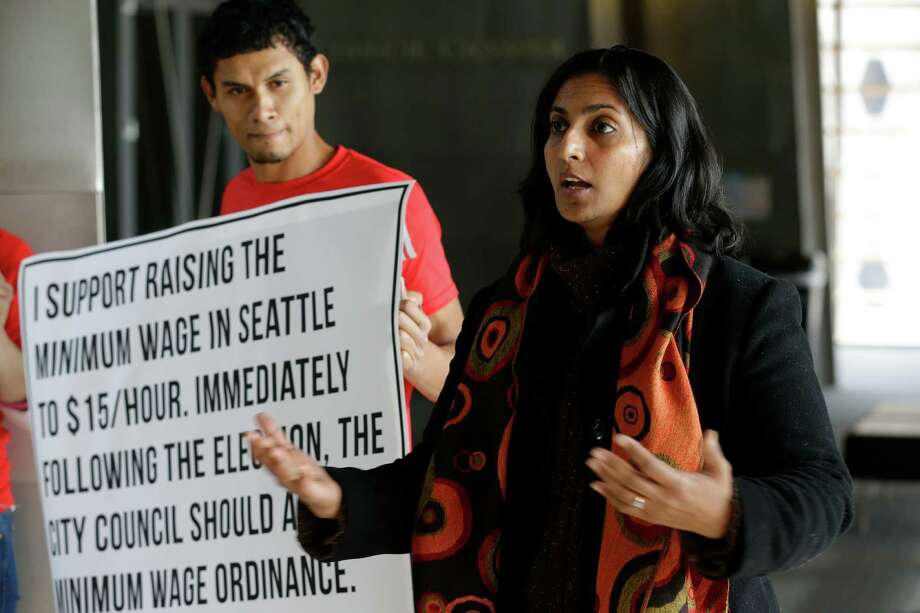 In this photo taken Nov. 4, 2013, Socialist candidate for Seattle City Council Kshama Sawant, right, speaks outside City Council chambers in Seattle about her support for raising the minimum wage to $15 an hour for all workers in the city. Sawant is challenging four-term Councilman Richard Conlin. Photo: Ted S. Warren, AP / AP2013
