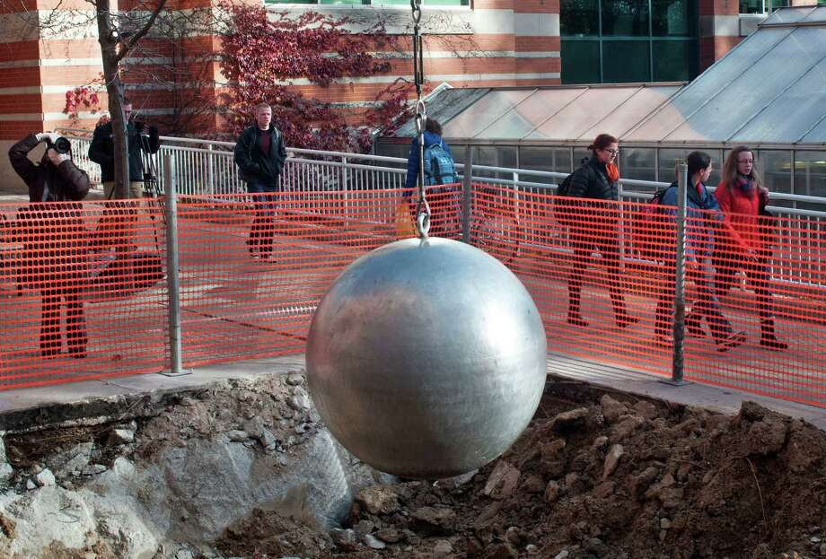 The pendulum sculpture near Grand Valley State University Padnos Hall of Science in Allendale, Mich., was reinstalled on Tuesday, Nov. 12, 2013. The swinging sculpture was removed from the school's grounds after students used it to mimic a Miley Cyrus video in which she rides, naked, on a wrecking ball. (AP Photo/The Grand Rapids Press, Chris Clark) Photo: Chris Clark, AP / The Grand Rapids Press