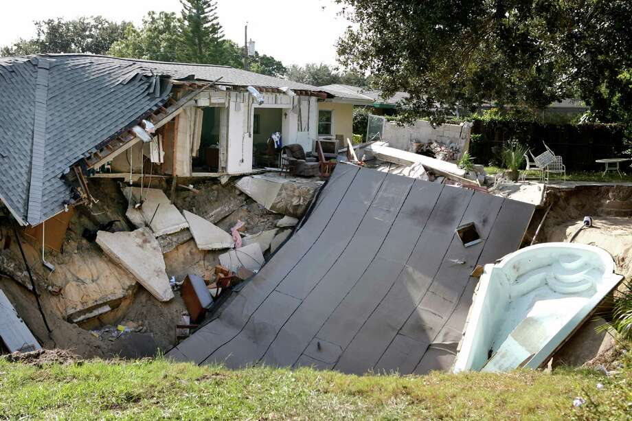 The home of Michael and Janni Dupre is destroyed after the backyard behind the home collapsed into a sinkhole, taking their patio and boat, on Thursday, Nov. 14, 2013. in Dunedin, Fla.  Dunedin Deputy Fire Chief Trip Barrs said the hole appeared to be about 12-feet wide when officials arrived on the scene. Residents of the neighboring houses also were evacuated as a precaution.  There are no reports of injuries. (AP Photo/The Tampa Bay Times, Douglas R. Clifford)  Photo: Douglas R. Clifford, AP / TAMPA BAY TIMES2013