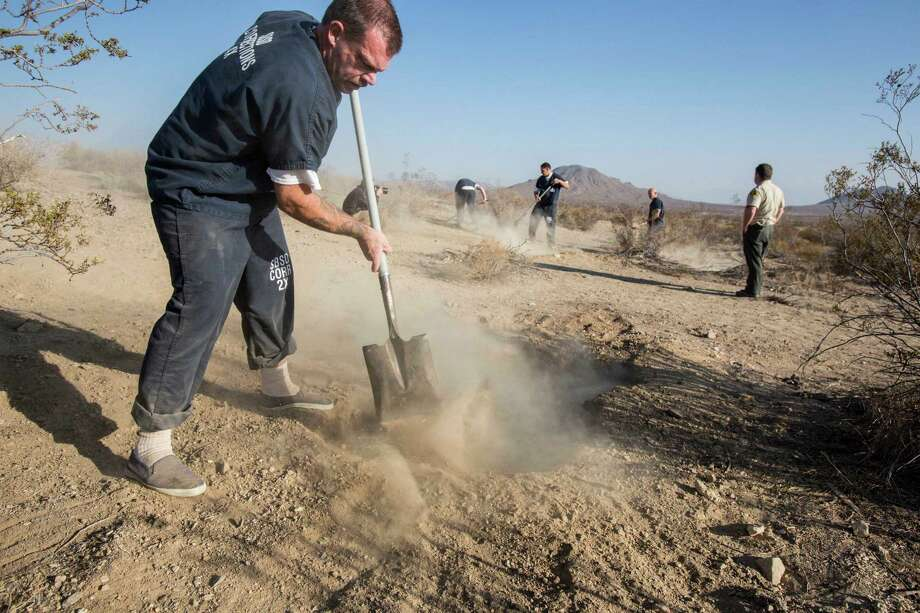 The workers fill the two shallow graves at the site on the outskirts of Victorville that contained the skeletal remains of members of missing McStay family on Friday, Nov. 15, 2013, in San Bernardino, Calif. San Bernardino County Sheriff Edward J. McMahon confirmed Joseph McStay and his 43-year-old wife, Summer, were found in shallow graves in the Mojave Desert this week. The couple and their two sons disappeared in February 2010. Photo: Ringo H.W. Chiu, AP / FR170512 AP