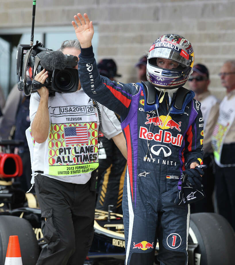 Current World Champion Sebastian Vettel waves to fans after capturing the pole position just edging out teammate Mark Webber for Sunday's Formula One United States Grand Prix at the Circuit of the Americas near Austin, Texas on Saturday, Nov. 16, 2013. The top three qualifiers are in order: Vettel, Webber and Lotus F1 driver Romain Grosjean. Photo: Kin Man Hui, San Antonio Express-News / ©2013 San Antonio Express-News