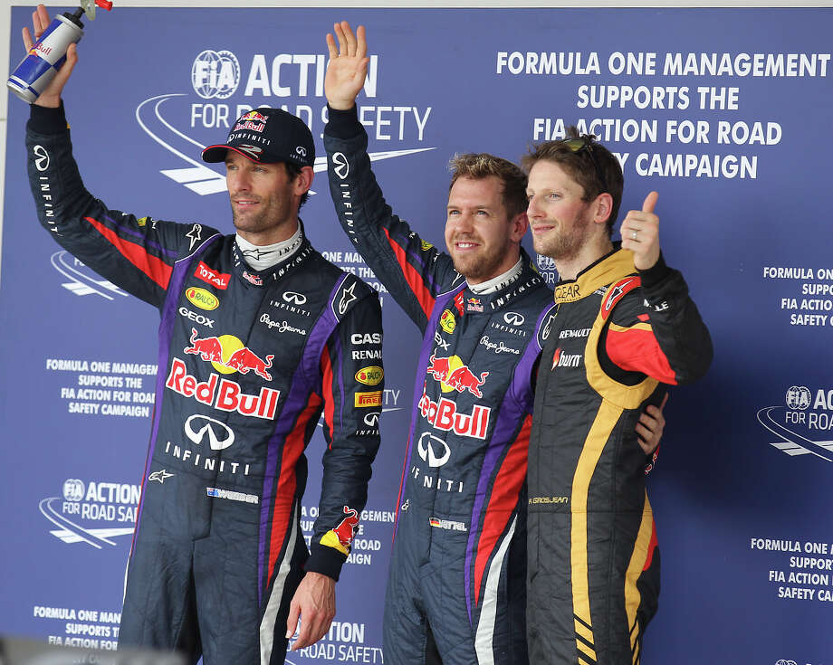 Current World Champion Sebastian Vettel (center) joins teammate Mark Webber (left) and Lotus F1 driver Romain Grosjean to represent the top three finishers in qualifying for Sunday's Formula One United States Grand Prix at the Circuit of the Americas near Austin, Texas on Saturday, Nov. 16, 2013. The top three qualifiers are in order: Vettel, Webber and Grosjean. Photo: Kin Man Hui, San Antonio Express-News / ©2013 San Antonio Express-News