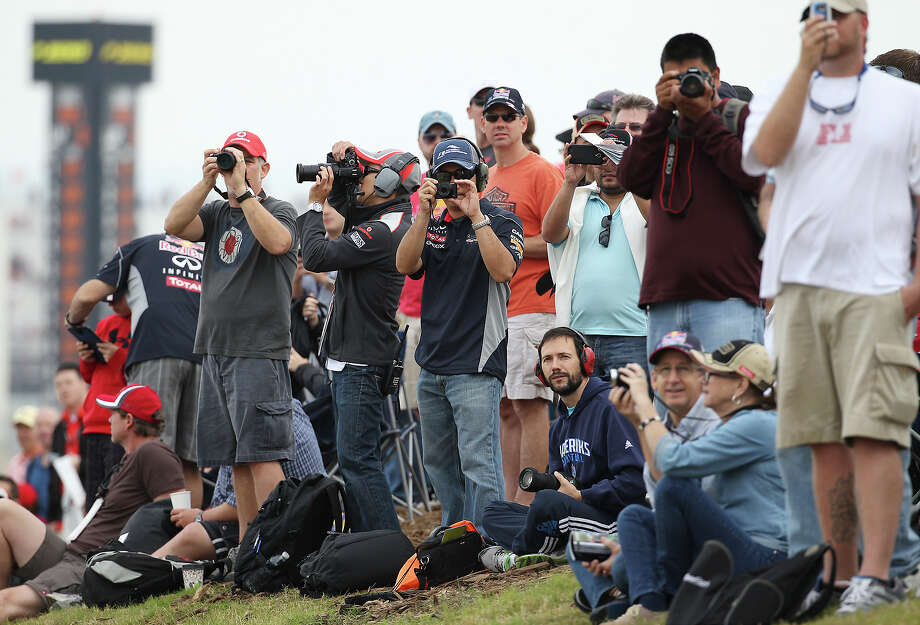 Racing fans attempt to photograph their favorite drivers during the Formula One United States Grand Prix morning practice session at the Circuit of the Americas near Austin, Texas on Saturday, Nov. 16, 2013. Photo: Kin Man Hui, San Antonio Express-News / ©2013 San Antonio Express-News