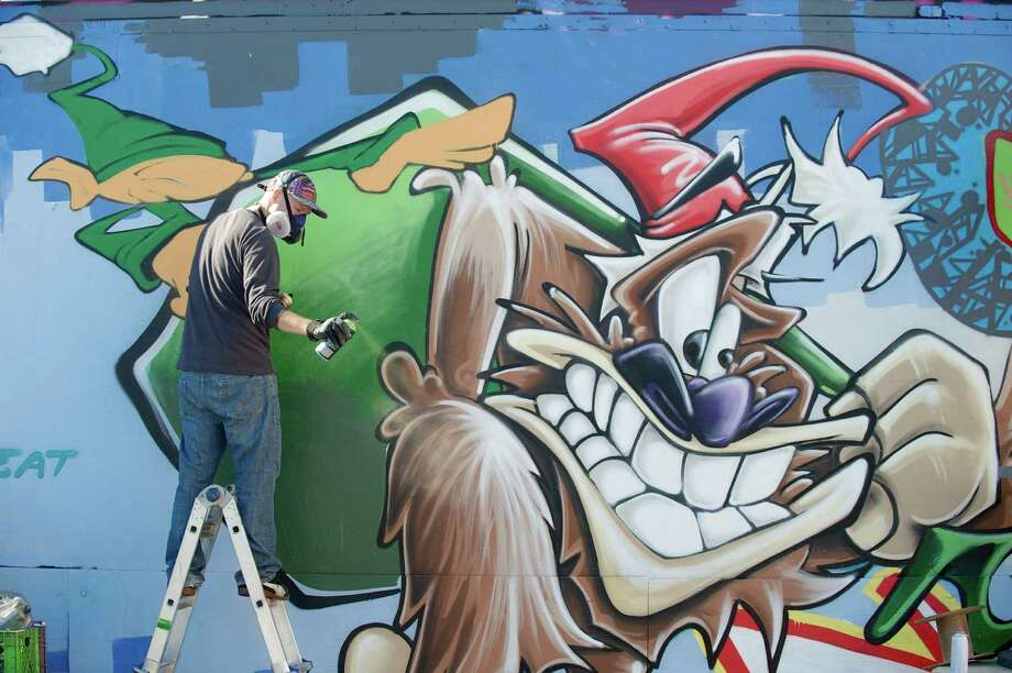 The artist Yedi Fresh, of New Fairfield, cleans the nozzle of his spray paint can while working on the 2013 Christmas Production at the Trailer Box Gallery in Danbury, Conn on Saturday, November 16, 2013. Graffiti and urban artists, from the Danbury area and as far away as Boston MA, got together to create the work. Photo: H John Voorhees III / The News-Times Freelance