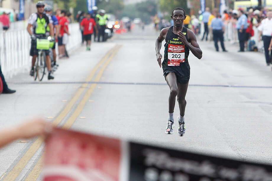 Abraham Rutto of Georgetown, Texas, approaches the finish line of the Half Marathon during the Rock 'n' Roll San Antonio Marathon and 1/2 Marathon on Sunday, Nov. 17, 2013.  Rutto won the 1/2 marathon race with a time of 1:07.16. Photo: Marvin Pfeiffer, San Antonio Express-News / Express-News 2013
