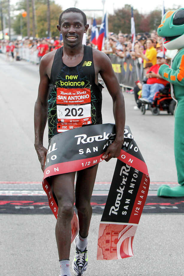 Abraham Rutto of Georgetown, Texas, crosses the finish line of the half marathon during the Rock 'n' Roll San Antonio Marathon and 1/2 Marathon on Sunday, Nov. 17, 2013.  Rutto took the men's title in the 1/2 marathon with a time of 1:07.16. Photo: Marvin Pfeiffer, San Antonio Express-News / Express-News 2013