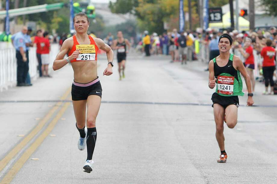 Dani Fisher (left) of Wausau, Wis., approaches the finish line of the half marathon during the Rock 'n' Roll San Antonio Marathon and 1/2 Marathon on Sunday, Nov. 17, 2013.  Fisher took the women's title in the 1/2 marathon with a time of 1:18.58. Photo: Marvin Pfeiffer, San Antonio Express-News / Express-News 2013