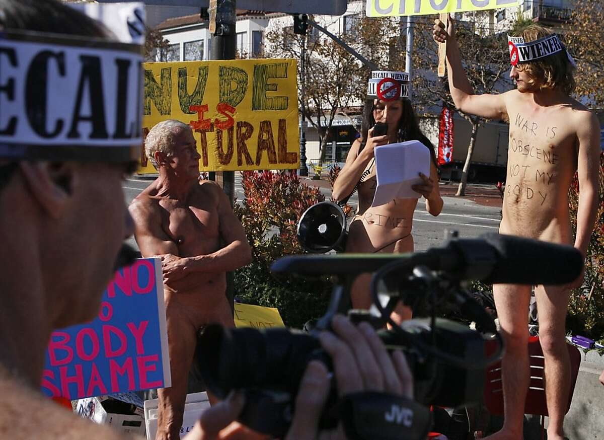 Chuck Newell records Rusty Mills, Gypsy Taub, and Jimmy Smith during a nudist protest at Castro st and Market st in San Francisco, Calif. on Sunday, Nov. 17, 2013. in San Francisco, Calif. on Sunday, Nov. 17, 2013.