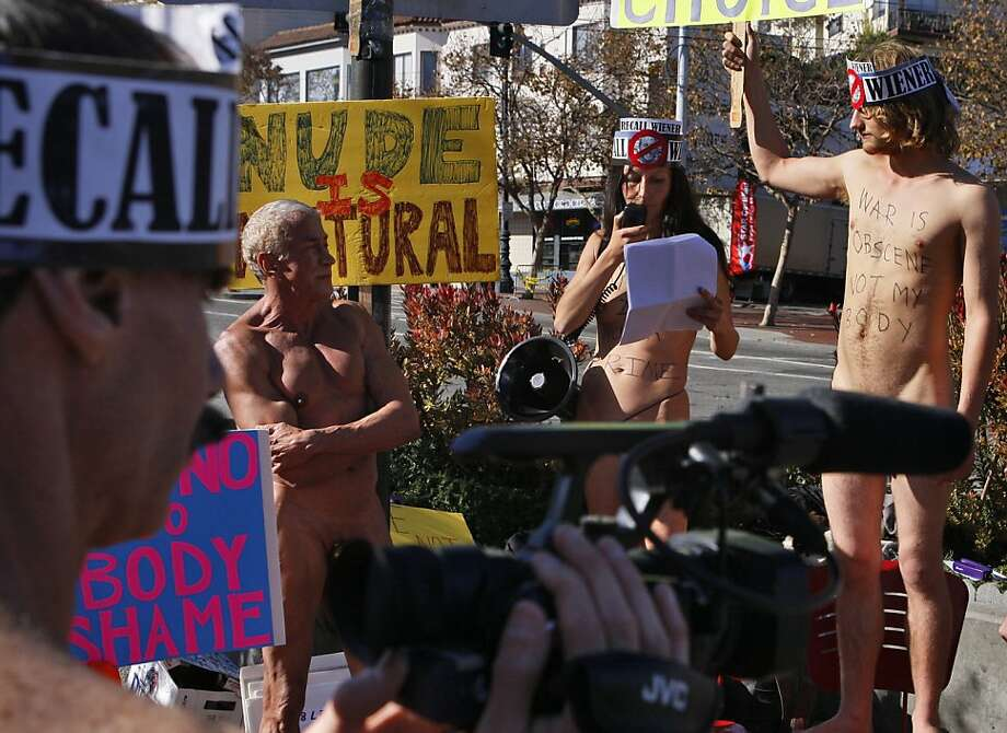 Chuck Newell documents the scene as Rusty Mills (left), Gypsy Taub and Jaymz Smith protest the city's public nudity ban at Castro and Market streets. Photo: Raphael Kluzniok, The Chronicle
