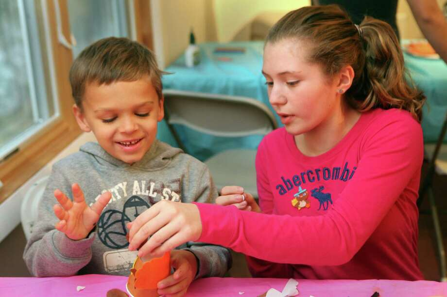 Alexandra Coclin, 12,  a TNAC member, helps William DeFeo, 6, with a Thanksgiving craft at  the Trumbull Nature and Arts Center on Sunday, Nov. 17, 2013. The TNAC is a Student Leadership in Environment, Culture, and Art team and plans to host an ornament event in December. Photo: Unknown, B.K. Angeletti / Connecticut Post freelance B.K. Angeletti