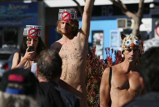 Gypsy Taub, Jimmy Smith, and Lloyd Fishback are seen over a small crowd during a nudist protest at Castro st and Market st in San Francisco, Calif. on Sunday, Nov. 17, 2013. in San Francisco, Calif. on Sunday, Nov. 17, 2013. Photo: Raphael Kluzniok, The Chronicle