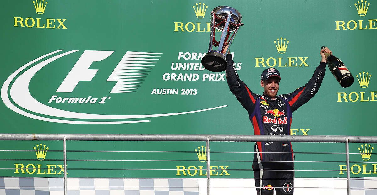 2013 USGP winner and current World Champion Sebastian Vettel acknowledges the crowd after The Formula One United States Grand Prix at the Circuit of the Americas near Austin, Texas on Sunday, Nov. 17, 2013. Vettel finished first followed by Lotus F1's Romain Grosjean and in third was Vettel's teammate, Mark Webber.