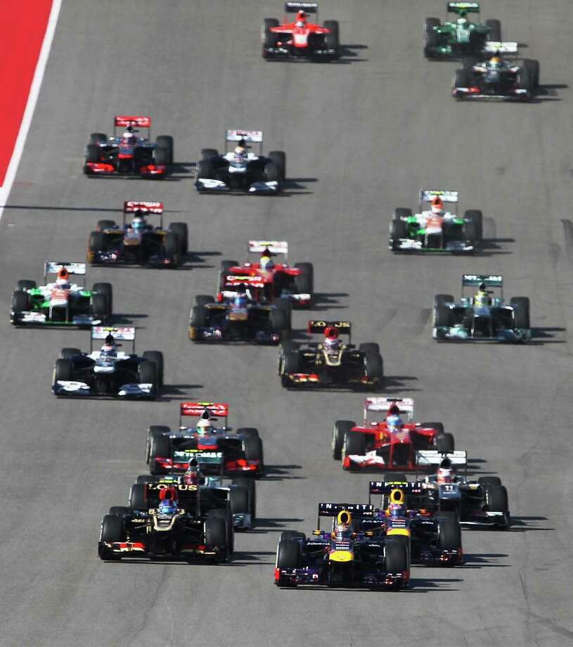 World Champion Sebastian Vettel (foreground) leads the pack to Turn 1 during The Formula One United States Grand Prix at the Circuit of the Americas near Austin, Texas on Sunday, Nov. 17,  2013. Vettle finished first followed by Lotus F1's Romain Grojean and in third was Vettel's teammate, Mark Webber. Photo: Kin Man Hui, San Antonio Express-News / ©2013 San Antonio Express-News