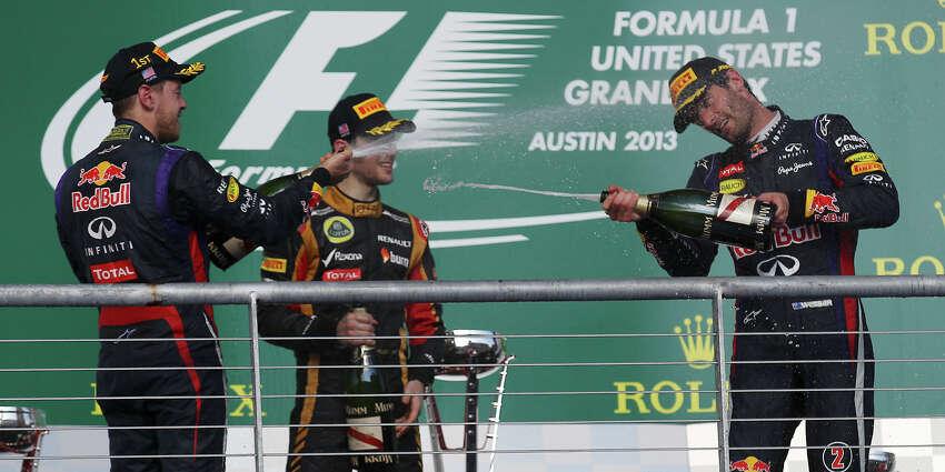 USGP Winner Sebastian Vettel (left) sprays champagne toward teammate and third place winner Mark Webber as second place winner Lotus F1 driver Romain Grosjean looks on after The Formula One United States Grand Prix at the Circuit of the Americas near Austin, Texas on Sunday, Nov. 17, 2013.