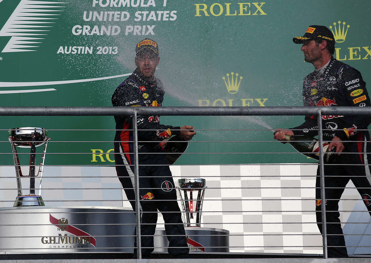 USGP Winner Sebastian Vettel (left) gets a spray of champagne from teammate and third place winner Mark Webber after The Formula One United States Grand Prix at the Circuit of the Americas near Austin, Texas on Sunday, Nov. 17, 2013.