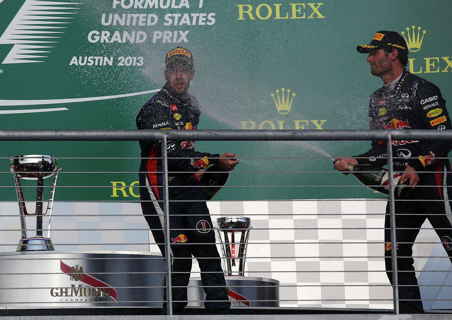 USGP Winner Sebastian Vettel (left) gets a spray of champagne from teammate and third place winner Mark Webber after The Formula One United States Grand Prix at the Circuit of the Americas near Austin, Texas on Sunday, Nov. 17,  2013. Photo: Kin Man Hui, San Antonio Express-News / ©2013 San Antonio Express-News