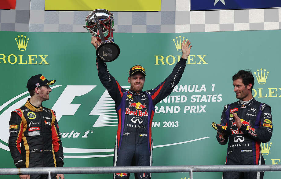 USGP Winner Sebastian Vettel (center) holds the first place trophy after winning the 2013 Formula One United States Grand Prix at the Circuit of the Americas near Austin, Texas on Sunday, Nov. 17,  2013. Lotus F1 driver Romain Grosjean finished second and Vettel's teammate Mark Webber finished in third. Photo: Kin Man Hui, San Antonio Express-News / ©2013 San Antonio Express-News